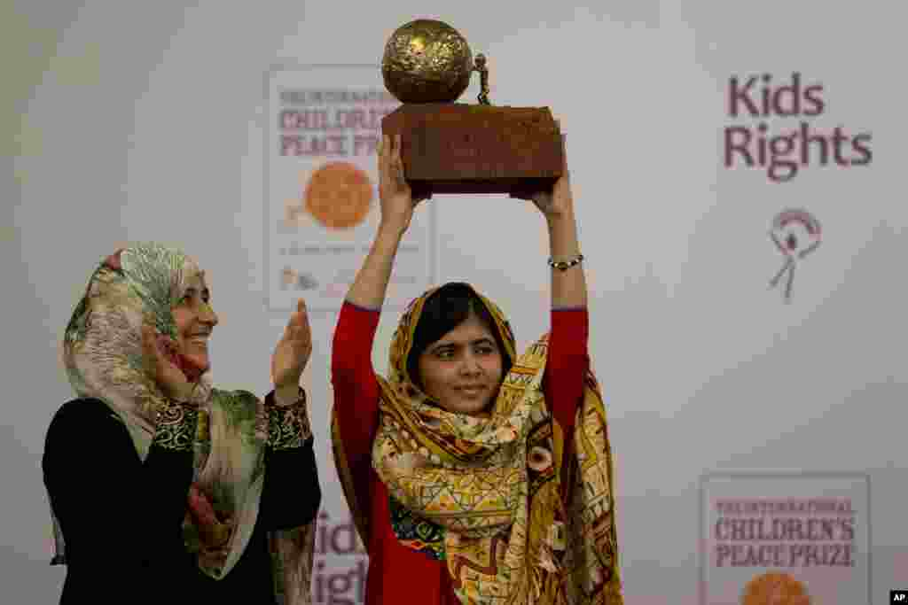 Pakistani teenager Malala Yousafzai, right, who was shot and injured by the Taliban for advocating girls' education, is awarded the International Children's Peace Prize 2013 by 2011 Nobel Peace Prize winner Tawakkol Karman of Yemen, left, during a ceremony in the Hall of Knights in The Hague, Netherlands.