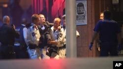 16일 호주 시드니 도심 인질극 현장에서 경찰이 부상한 인질을 구급차로 옮기고 있다.