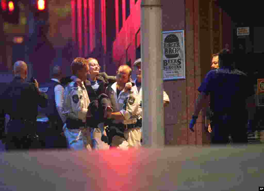 A injured hostage is carried to an ambulance after shots were fired during a cafe siege at Martin Place in the central business district of Sydney, Dec. 16, 2014.
