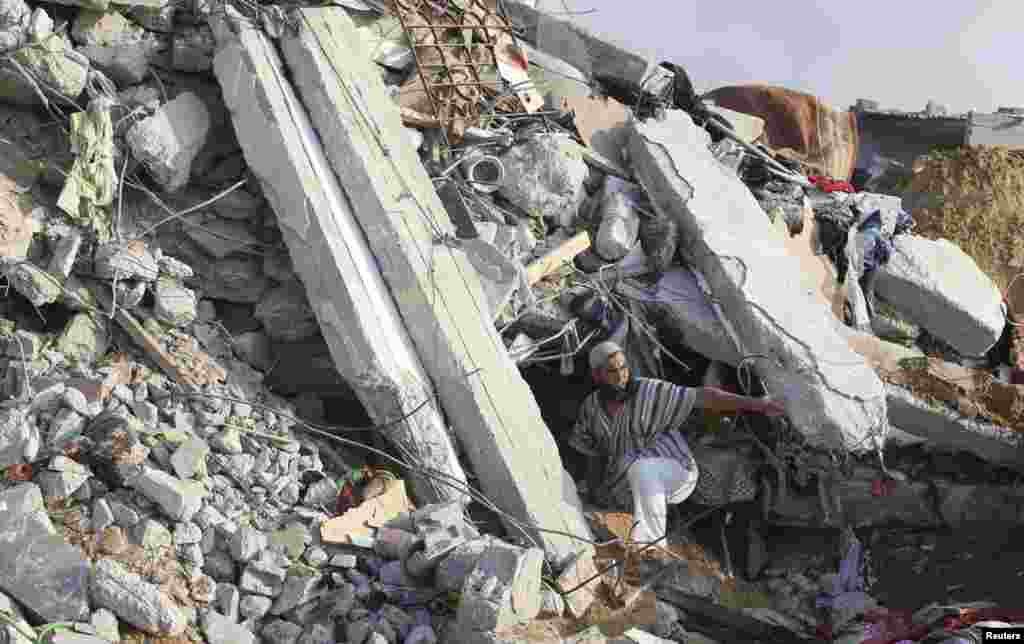 A Palestinian man searches for victims under the rubble of a house destroyed in an Israeli airstrike, in Rafah in the southern Gaza Strip, July 29, 2014.