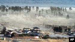 A massive tsunami sweeps in to engulf a residential area after a powerful earthquake in Natori, Miyagi Prefecture in northeastern Japan March 11, 2011.