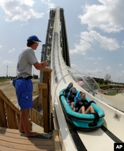 """FILE - In this photo taken with the fisheye lens, riders go down the world's tallest water slide called """"Verruckt"""" at Schlitterbahn Waterpark in Kansas City, Kan., July 9, 2014."""