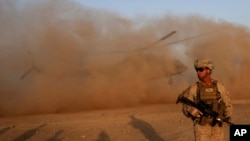 FILE - A U.S. Marine takes part during a training session for Afghan army commandos in Shorab military camp in Helmand province, Afghanistan, Aug. 27, 2017.