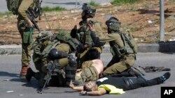 Binh sĩ Israel sơ cứu một đồng đội bị đâm bởi một người Palestine (mặc áo khoác màu vàng) trong cuộc đụng độ ở Bờ Tây, ngày 16/10/ 2015.