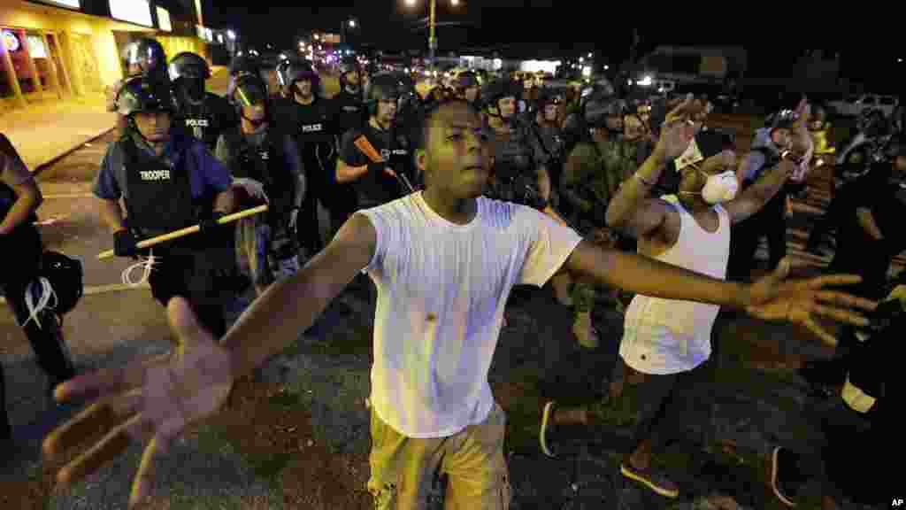 People are moved by a line of police as authorities disperse a protest in Ferguson, Missouri, early Aug. 20, 2014.