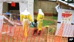 Wafanyakazi wa afya wakiwa wamemshikilia mtoto aliyeshukiwa kuwa na virusi vya Ebola huko Beni, DRC mwaka 2018