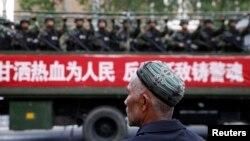 Một người đàn ông Hồi giáo Uighur đang nhìn theo chiếc xe tải chở lực lượng vũ trang bán quân sự trên đường phố trong một chiến dịch chống khủng bố của chính quyền Trung Quốc ở Tân Cương.