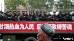 Truk yang membawa polisi paramiliter di Xinjiang, China.