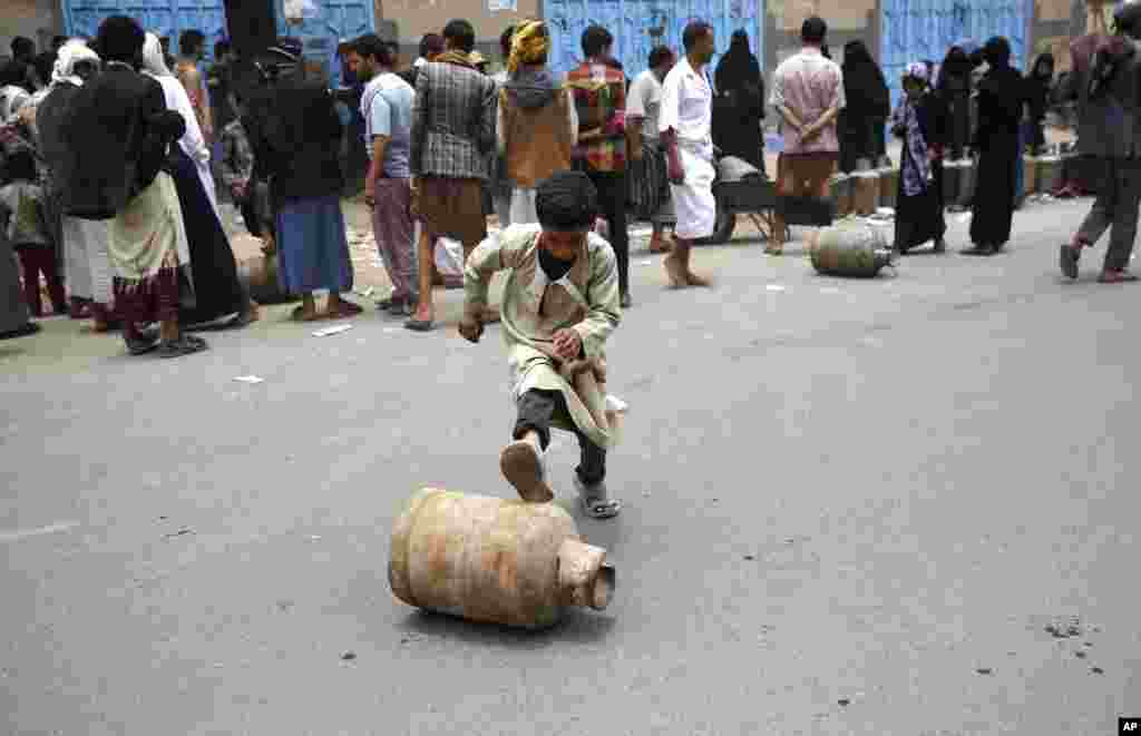A Yemeni boy rolls a canister of gas he bought, after waiting for hours in Sana'a, Yemen. The Saudi-imposed blockade has created severe shortages of gas, petrol, and other goods, causing prices to skyrocket.