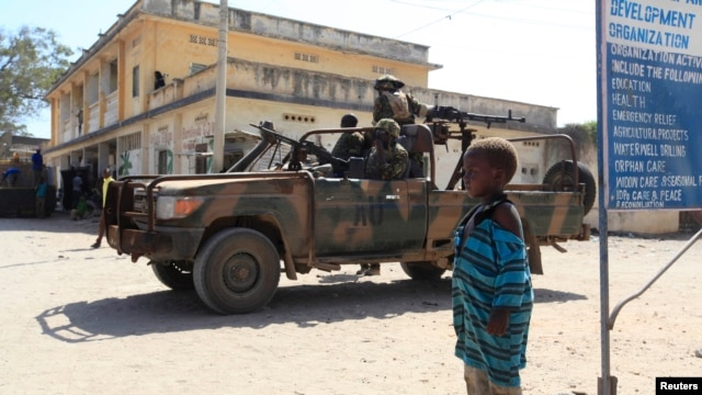 FILE - A boy looks on as Kenya Defense Force (KDF) soldiers, serving in the African Union Mission in Somalia (AMISOM), patrol the streets of Somalia's Kismayo town in lower Juba region, February 26, 2013.