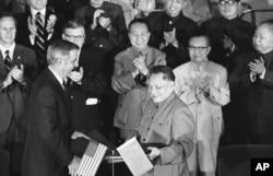 1979年8月28日,美国副总统蒙代尔和中国副总理邓小平在两国文化和水电协议书签署后,交换协议文本。前排鼓掌者有中国总理华国锋(中)、美国驻华大使伦纳德•伍德科克(华国锋左侧)和中国外交部长黄华(华国锋右侧)