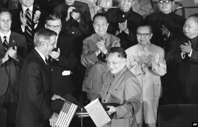 1979年8月28日,美國副總統蒙代爾和中國副總理鄧小平在兩國文化和水電協議書籤署後,交換協議文本。 前排鼓掌者有中國總理華國鋒(中)、美國駐華大使倫納德•伍德科克(華國鋒左側)和中國外交部長黃華(華國鋒右側)
