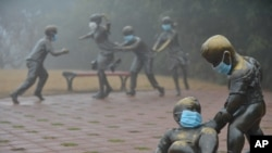 2017年1月4日,河南濮陽,在霧霾裡,街頭雕塑也被戴上口罩
