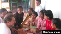 Fred Bemak, left front, talks with Burmese children post-cyclone. (Courtesy of Fred Bemak and Rita Chung)
