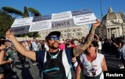 FILE - Protesters demonstrate against the Green Pass plan (health pass) that has become mandatory to access an array of services and leisure activities, in Rome, Italy, Aug. 7, 2021.