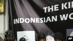 Indonesian activists wear the names of four Indonesian women, who were allegedly tortured by their employers in Saudi Arabia, stand in front of the Saudi Arabian Embassy during a demonstration, Aug. 13, 2007 in Jakarta, Indonesia.