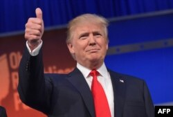 Donald Trump flashes the thumbs-up as he arrives on stage for the start of a Republican presidential debate, Aug. 6, 2015, in Cleveland, Ohio.