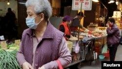 台灣一名婦人帶上口罩在一個露天菜市場走過。