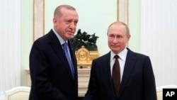 Arhiv- Ruski predsjednik Vladimir Putin i turski predsjednik Recep Tayyip Erdogan rukuju se za vrijeme sastanka u Kremlju, 5. marta 2020.