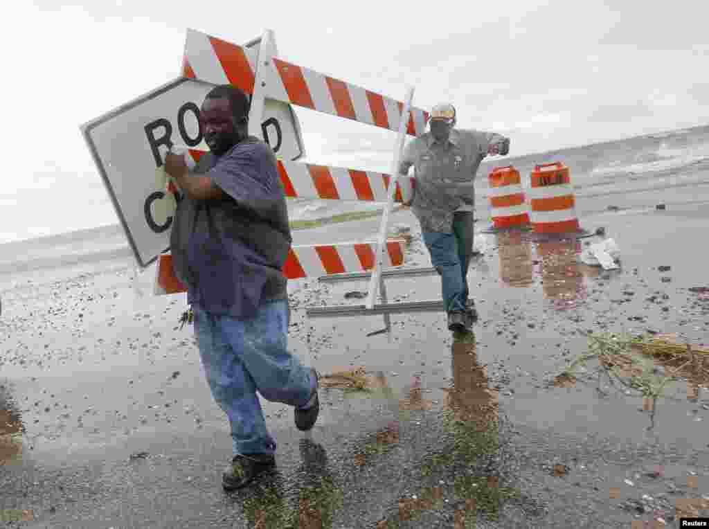 Employees of the Orleans Levee District remove signs from Lake Shore Dr. near the shore of Lake Pontchartrain as tropical storm Isaac approaches New Orleans, August 28, 2012.