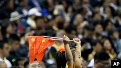 一个小女孩在上海举着两面中国国旗观看布鲁克林篮网队和洛杉矶湖人队的篮球比赛。(2019年10月10日)