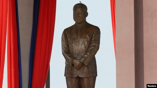 A bird stands on the head of a statue of the late King Norodom Sihanouk during the statue's unveiling ceremony in central Phnom Penh, Oct. 11, 2013.