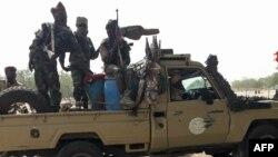 Des soldats de l'armée tchadienne sont assis à l'arrière d'un Land Cruiser au marché de Koundoul, à 25 km de N'Djamena, le 3 janvier 2020, à leur retour après une mission de plusieurs mois contre Boko Haram au Nigeria.