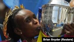 Rita Jeptoo du Kenya porte le trophée après sa victoire au 118e marathon de Boston version féminine, à Boston, Massachusetts, 21 avril 2014. REUTERS / Brian Snyder