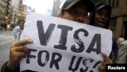Một người biểu tình cầm bich chương kêu gọi cấp visa cho người tị nạn tại Nhật Bản trong cuộc biểu tình tại trung tâm Tokyo ngày 9/9/2015.