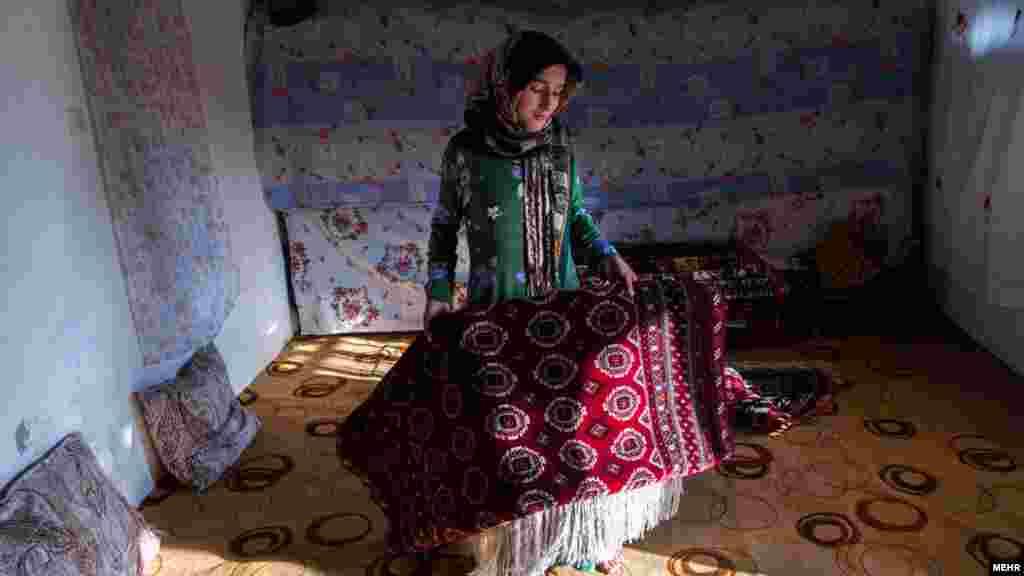 دختر قالیباف در حال بلند کردن فرش طرح ترکمنی که بافته است. مهر عکس هایی از زنان و دختران قالیباف خراسان شمالی با عنوان «زنان پنجه طلا» منتشر کرد. عکس: فاطمه عابدی
