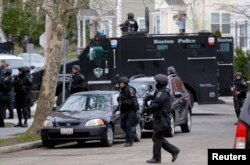 FILE - SWAT teams enter a suburban neighborhood searching for the remaining suspect in the Boston Marathon bombings in Watertown, Massachusetts, April 19, 2013.