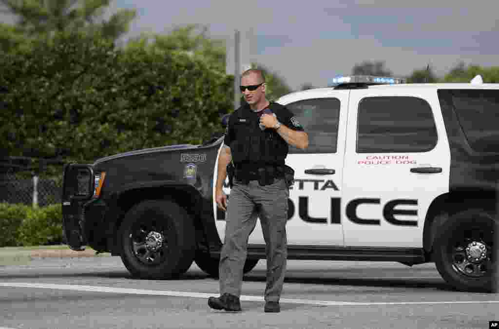 A Marietta police officer stops traffic during the morning commute on the busy U.S. Highway 41 while a motorcade transporting an American infected with the deadly Ebola virus from West Africa leaves Dobbins Air Reserve Base, Marietta, Georgia, Sept. 9, 2014.