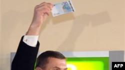 Thủ tướng Estonia Andrus Ansip giơ cao tờ 20 euro vừa rút khỏi máy rút tiền