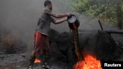 FILE - A man working at an illegal oil refinery site pours oil under a locally made burner to keep the fire going, near river Nun in Nigeria's oil state of Bayelsa.