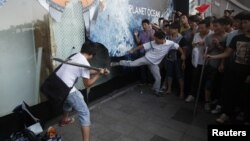 Protestantes golpean una ventana publicitaria en una tienda la departamentos japonesa Seibu en China.