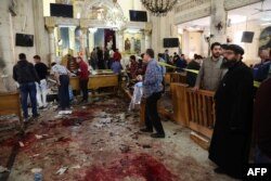 FILE - People look at the aftermath following a bomb blast which struck worshippers gathering to celebrate Palm Sunday at the Mar Girgis Coptic Church in the Nile Delta City of Tanta, 120 kilometres (75 miles) north of Cairo, April 9, 2017.