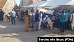 Une centaine de personnes font la queue pour accéder à la salle d'enrôlement à Dakar, au Sénégal, le 14 septembre 2018. (VOA/Seydina Aba Gueye)