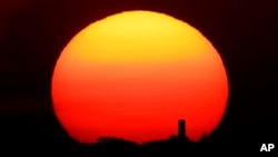 In this Friday, June 26, 2020 file photo, the sun sets behind a smokestack in the distance in Kansas City, Missouri. (AP Photo/Charlie Riedel, File)