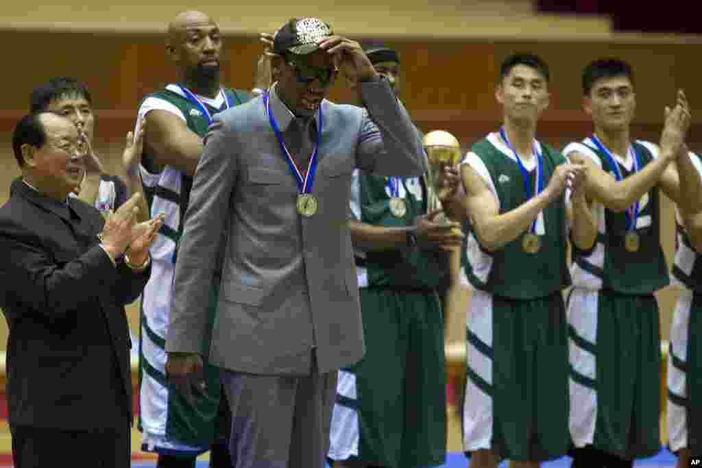 Dennis Rodman levanta o chapéu enquanto jogadores americanos e norte-coreanos aplaudem no final do jogo de basquetebol em Pyongyang, Jan. 8, 2014.