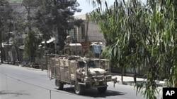 北约一辆坦克在坎大哈大街上巡逻