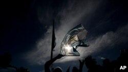 Un manifestante ondea una bandera nacional durante una protesta por el manejo de las vacunas COVID-19, en Buenos Aires, Argentina. Febrero 27, 2021. Foto: AP.