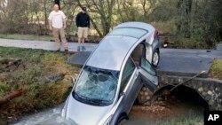 Hai cha con ông Mitchell đứng cạnh chiếc xe chở 4 người bị lũ quét ra khỏi đường phố hôm thứ bảy ngày 26 tháng 12, 2015 tại Pinson, Alabama.