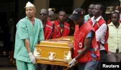 Mortuary workers and Kenya Red Cross volunteers carry the coffin containing the body of Mildred Yondo, a student killed during an attack by gunmen at Garissa University, from the Chiromo Mortuary in the capital Nairobi, April 8, 2015.