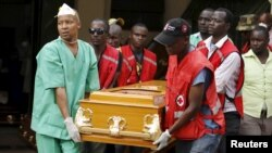 FILE - Mortuary workers and Kenya Red Cross volunteers carry the coffin of a student killed April 2 by gunmen at Garissa University College, from the Chiromo Mortuary in the capital Nairobi, April 8, 2015.