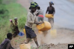 FILE - A girl sifts roadside sand to separate the stones to sell as building material in Inchope, northern Mozambique.