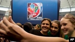 Cầu thủ Christine Sinclair của đội tuyển Canada chụp hình với người hâm mộ bên huy hiệu của World Cup Bóng đá nữ Canada 2015.