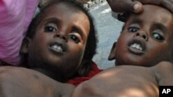 Two Somali children suffering from malnutrition lie at a camp for internally displaced people near Mogadishu airport, July 18, 2011.