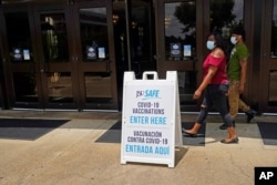 FILE - Masked students walk to a COVID-19 vaccination site at the Rose E. McCoy Auditorium on the Jackson State University campus in Jackson, Mississippi., July 27, 2021.