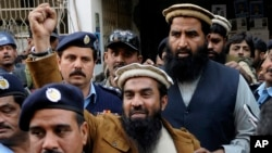 In this Thursday, Jan. 1, 2015 file photo, Zaki-ur-Rehman Lakhvi, the main suspect of the Mumbai terror attacks in 2008, raises his fist after his court appearance in Islamabad, Pakistan.