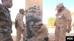 Pejuang Anti-Gaddafi merobohkan gerbang yang semula dibuat untuk pembatas wilayah kota Sirte dengan kota terdekatnya yang berjarak hampir 50 kilometer ke arah Timur (5/10).